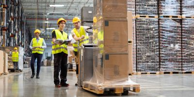 Employees Consult While Working In The Warehouse V2L6TMN